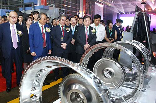 Các đại biểu tham quan sản phẩm cấu kiện động cơ máy bay. Ảnh: Lê Tiên.